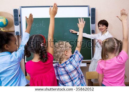Image of pupils stretching their hands during the lesson - stock photo