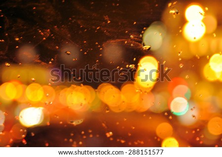 Image of raindrops on window at night in city  - stock photo