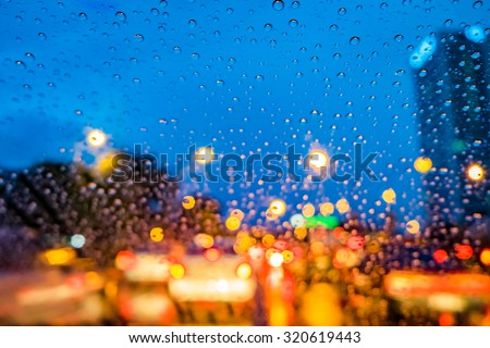 Image of raindrops on window at night in the city. Street Bokeh Lights defocused. - stock photo
