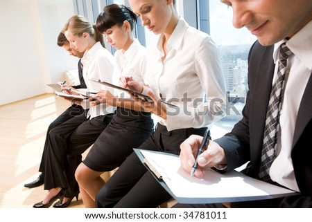 Image of row of business people writing on papers at seminar - stock photo