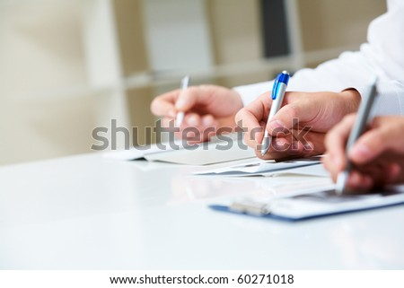 Image of row of human hands writing on papers at seminar - stock photo
