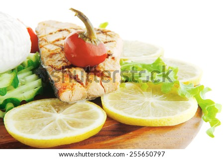 image of salmon with lemon and tomatoes on wood - stock photo