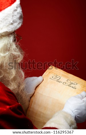 Image of Santa Claus reading Christmas letter in his hands - stock photo