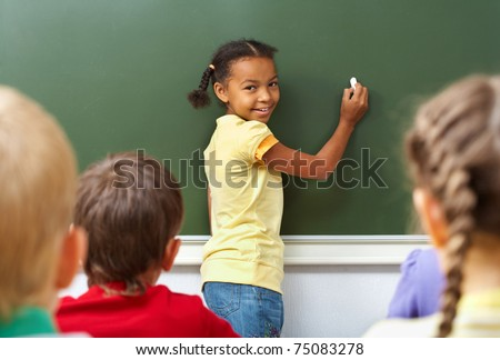 Image of schoolgirl by the blackboard looking at camera through classmates - stock photo