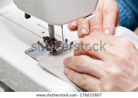 Image of seamstress working on sewing machine. - stock photo