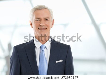 Image of senior bank manager standing at office and looking at camera. Business person. - stock photo