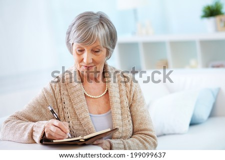 Image of senior female making notes in notepad - stock photo