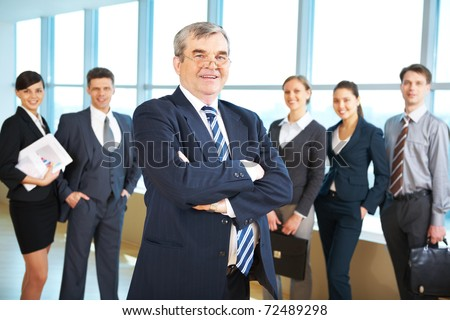Image of senior leader smiling at camera with several employees behind - stock photo