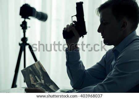 Image of serial killer with gun waiting in room - stock photo