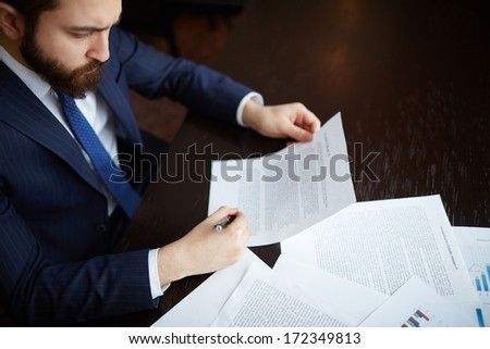 Image of serious businessman signing contract at workplace - stock photo