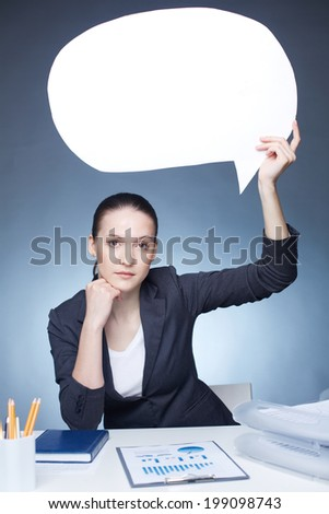 Image of serious businesswoman with paper speech bubble in her hand looking at camera - stock photo