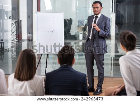 Image of several business people are looking at successful specialist is explaining new project at board. - stock photo