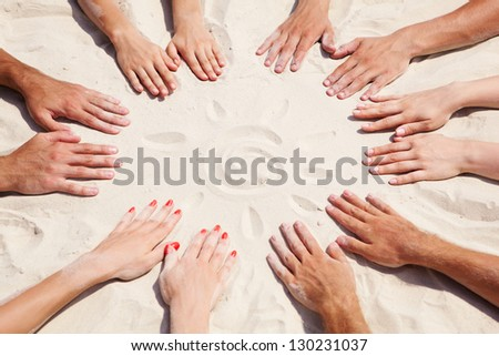 Image of several hands on sand in the form of circle with sun in center - stock photo