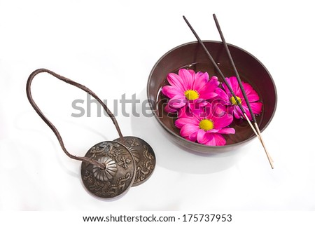 Image of several objects used in Buddhist alternative therapies: tingsha bells, Tibetan singing bowl, massage oil and incense sticks. Image on white background. - stock photo