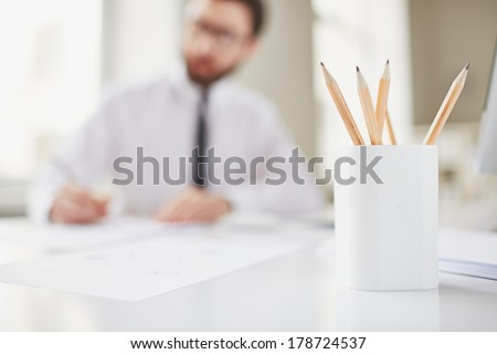 Image of several pencils on background of working businessman - stock photo