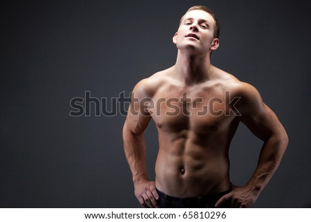 Image of shirtless man in jeans posing in front of camera - stock photo