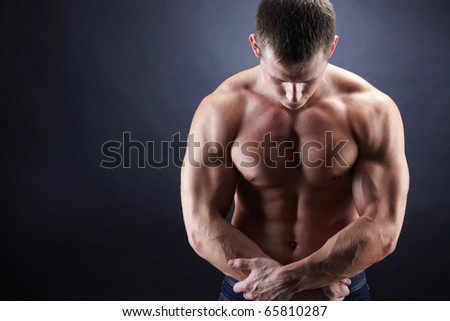Image of shirtless man looking downwards with his arms crossed by stomach - stock photo