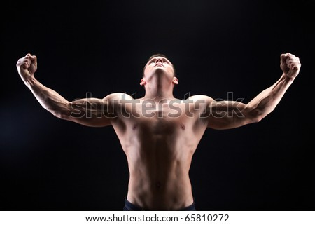 Image of shirtless man looking upwards with raised arms in front of camera - stock photo