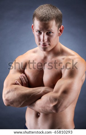 Image of shirtless man with crossed arms looking at camera over dark background - stock photo