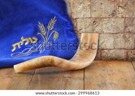 image of shofar (horn) and prayer case with word talit (prayer) writen on itin front of jerusalem ancient wall. rosh hashanah (jewish holiday) concept . traditional holiday symbol. - stock photo