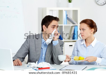 Image of sick businessman looking at his secretary giving him a cup of tea and lemon in office - stock photo