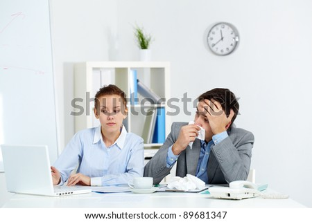 Image of sick businessman with tissue looking at laptop screen being pointed at by his colleague in office - stock photo