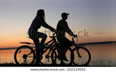 Image of silhouette sporty couple on bicycles outdoors against  water in sea texture  blue and yellow sunset sky. Copy space for inscription - stock photo