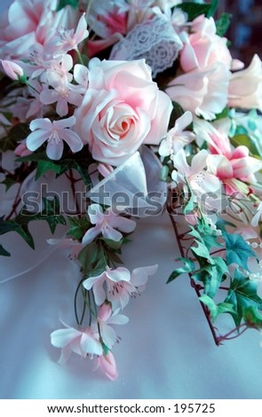 image of silk flower bridal bouquet with green leaves and bow. - stock photo