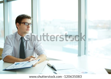 Image of smart businessman with document looking in the office window - stock photo