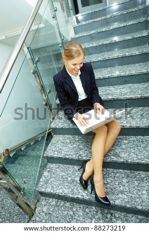 Image of smart businesswoman with laptop working on staircase - stock photo