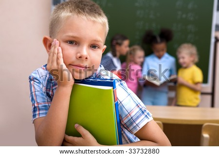 Image of smart schoolboy looking at camera with smile on background of classmates - stock photo