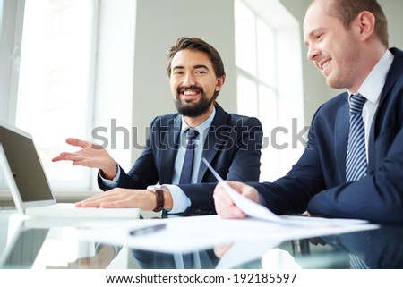 Image of smiling businessman pointing at laptop screen while explaining ideas to his colleague at meeting and looking at camera - stock photo
