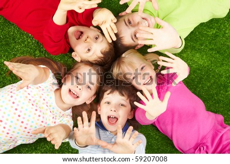 Image of smiling young boys and girls lying on green grass and showing palms - stock photo