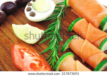 image of smoked salmon rolls on wooden plate - stock photo