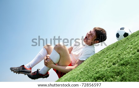 Image of soccer player lying down and shouting in pain - stock photo