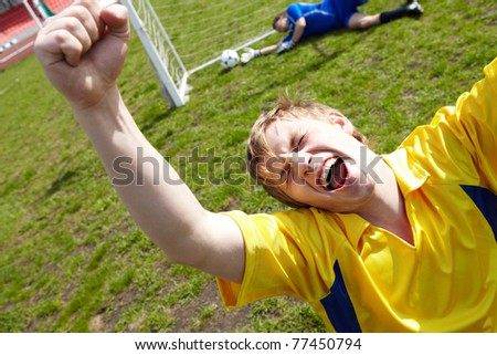 Image of soccer player shouting in joy - stock photo