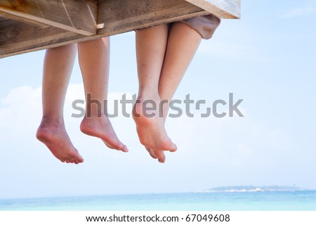 Image of soles of two people lying on sandy beach - stock photo