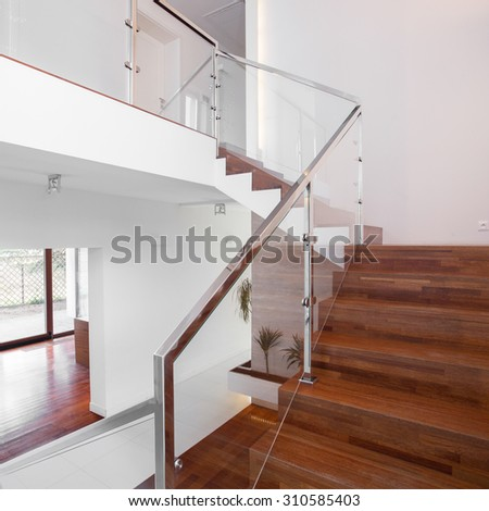 Image of solid wooden stairs with elegant glass balustrade - stock photo