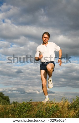 Image of sportsman running down green grass with grey sky at background - stock photo