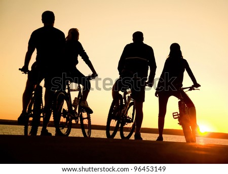 Image of sporty company  friends on bicycles outdoors against sunset. Silhouette. - stock photo