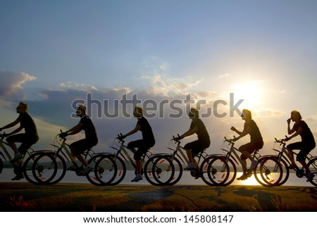 Image of sporty company friends on bicycles outdoors against sunset. Silhouette A lot phases of motion of a single cyclist along the shoreline coast Reflection on water copy Space for inscription - stock photo