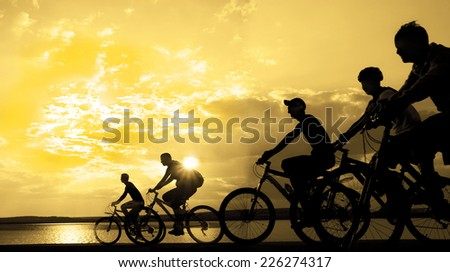 Image of sporty company friends on bicycles outdoors against sunset. Silhouette A lot phases of motion go of five 5 cyclist along shoreline coast Reflection sun on water Copy Space for inscription - stock photo