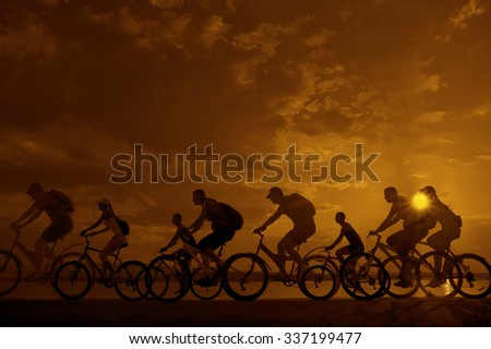 Image of sporty company friends on bicycles outdoors against sunset. Silhouette A lot phases of motion go of eight 8 cyclist along shoreline coast Reflection sun on water Copy Space for inscription - stock photo