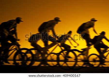 Image of sporty company friends on bicycles outdoors against sunset. Silhouette A lot phases of motion go of nine 9 cyclist along shoreline coast Reflection sun on water Copy Space for inscription - stock photo