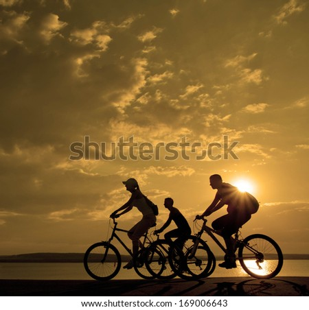 Image of sporty company three friends on bicycles outdoors against sunset. Silhouette motion of 3 cyclist along the shoreline coast and cloudy sunset sky Space for inscription - stock photo