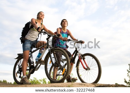 Image of sporty couple on bicycles outdoors against cloudy sky - stock photo