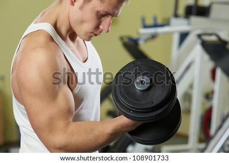 Image of sporty man training in gym with barbell - stock photo