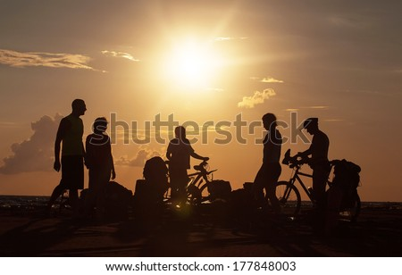 Image of sporty tourist company friends on bicycles outdoors against sunset near the sea and in the clouds. Silhouette people, mountainbike, backpacks, helmets. - stock photo