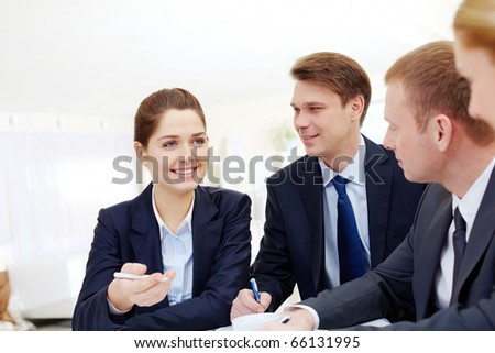 Image of successful employee explaining something to colleagues at meeting - stock photo