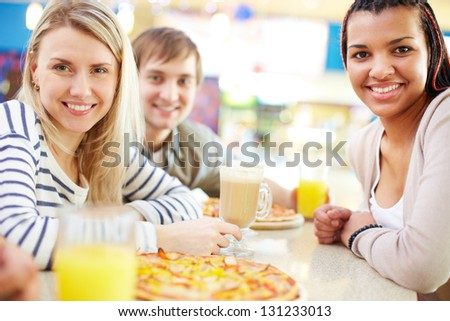 Image of teenage girlfriends looking at camera in cafe - stock photo